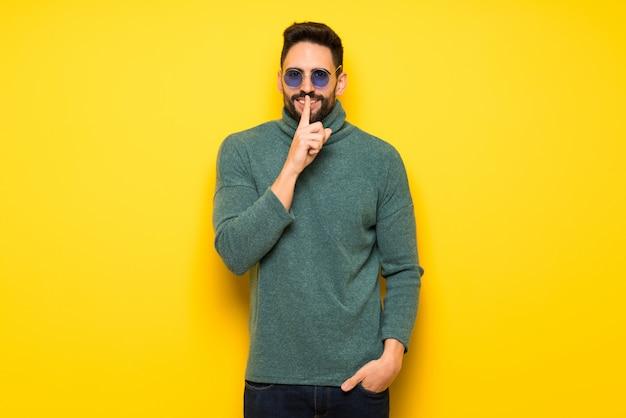 Przystojny mężczyzna z okularami przeciwsłonecznymi pokazuje znaka cisza gest