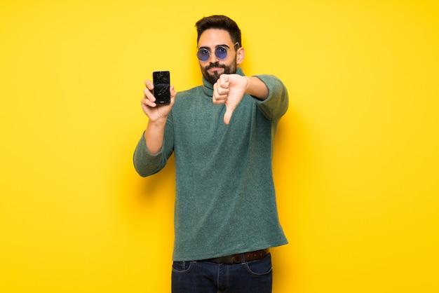Przystojny mężczyzna z okularami przeciwsłonecznymi z skołatanym mienia łamającym smartphone