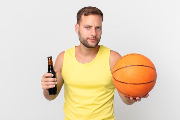Przystojny mężczyzna z piwem i piłką do koszykówki. świętować zwycięstwo