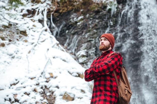 Przystojny mężczyzna z plecakiem stojący w pobliżu wodospadu na zewnątrz i odwracający wzrok
