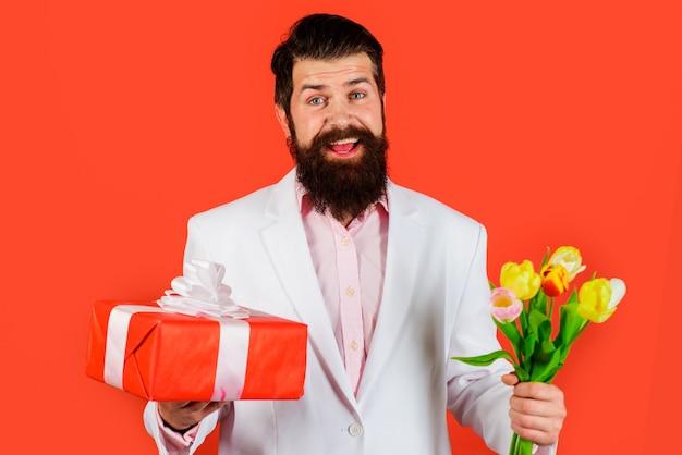 Przystojny mężczyzna z prezentem i kwiatami. biznesmen z tulipanami i teraźniejszością. walentynki