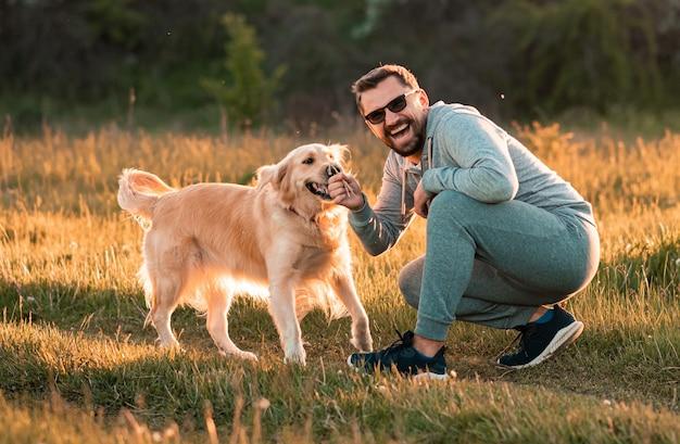 Przystojny mężczyzna z psem golden retriever spacer po jesiennej łące