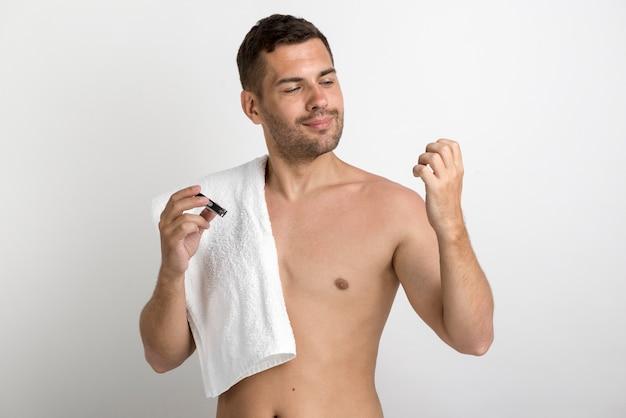 Przystojny mężczyzna z ręcznikiem i patrząc na swoje paznokcie, trzymając nożyczki do paznokci