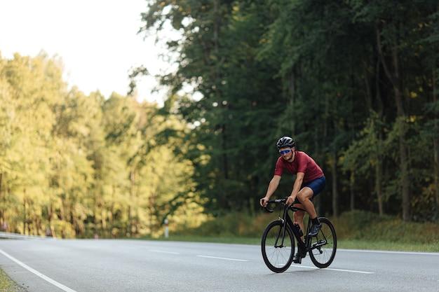 Przystojny mężczyzna z silnymi nogami dong rano ćwiczenia na rowerze na utwardzonej drodze.