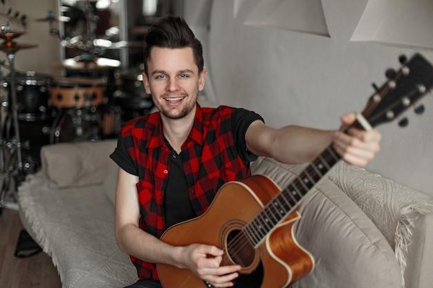 Przystojny mężczyzna z uśmiechem gra na gitarze