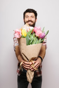 Przystojny mężczyzna zakochany życzący szczęśliwych walentynek, dając bukiet kwiatów na romantyczną randkę, uśmiechnięty, ubrany w garnitur na białej ścianie
