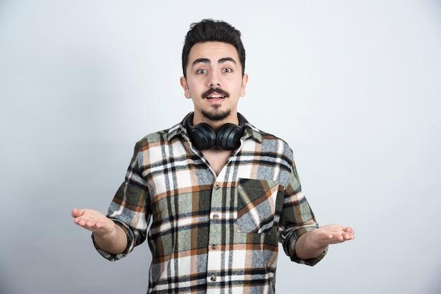 Przystojny mężczyzna ze słuchawkami stojący nad białą ścianą.