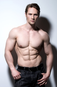 Przystojny mężczyzna ze stawianiem sexy mięśni piękne ciało