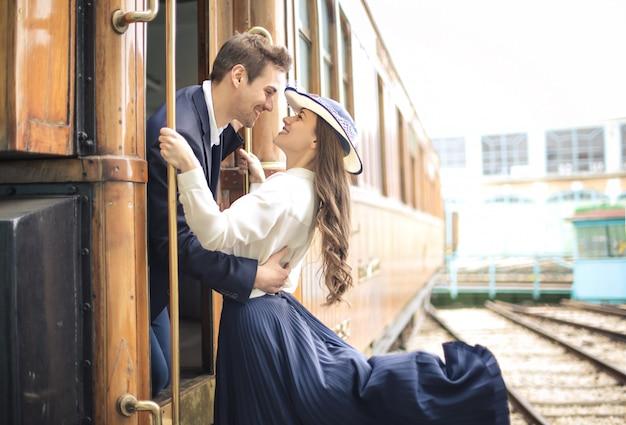 Przystojny mężczyzna żegna się ze swoją dziewczyną tuż przed odjazdem pociągu