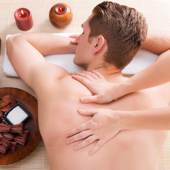 Przystojny mężczyzna zrelaksowany i cieszący się głębokim masażem pleców w salonie spa.