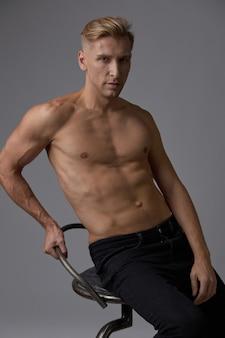 Przystojny mięśni młody człowiek pozowanie