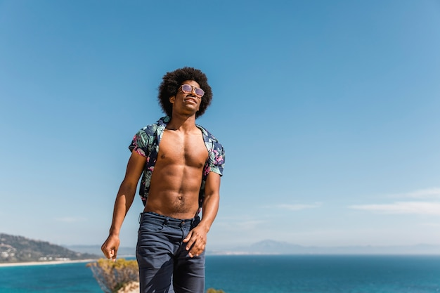 Przystojny mięśniowy afroamerykański mężczyzna pozuje na niebieskiego nieba i morza tle