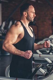 Przystojny mięśniowy mężczyzna biega na bieżni w gym.