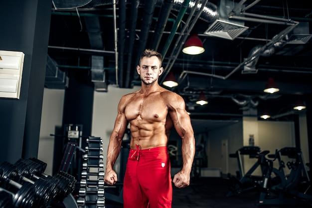 Przystojny mięśniowy mężczyzna pozuje przy gym