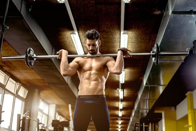 Przystojny mięśniowy mężczyzna pracujący przy gym out.