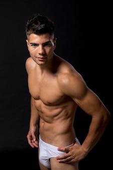 Przystojny mięśniowy młody człowiek pozuje w studiu