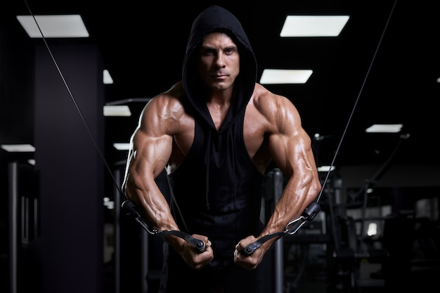 Przystojny mięśniowy seksowny mężczyzna pozuje w gym. opalony sportowiec