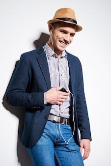 Przystojny miłośnik muzyki. przystojny młody mężczyzna w fedorze słucha odtwarzacza mp3 i uśmiecha się, opierając się o ścianę