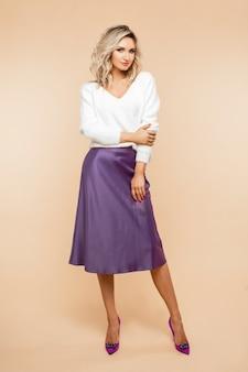 Przystojny młoda kobieta pozuje do kamery w bluzkę i spódnicę na białym tle na brzoskwiniowym miejscu