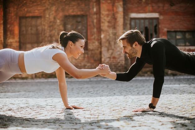 Przystojny młoda para doung jedno ramię ćwiczenia pushup w środowisku miejskim