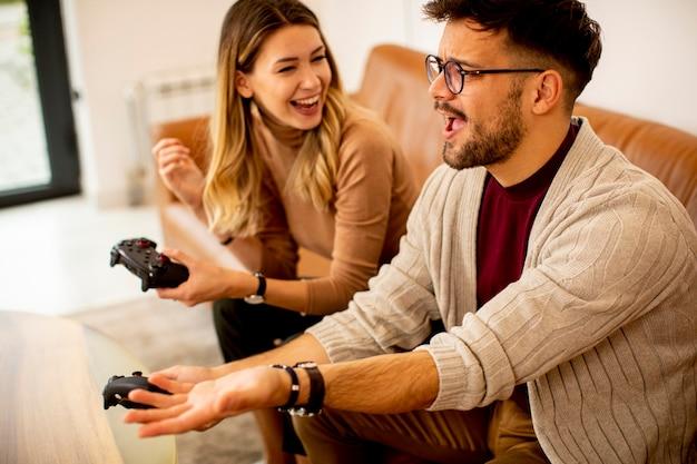Przystojny młoda para grając w gry wideo w domu, siedząc na kanapie i zabawie