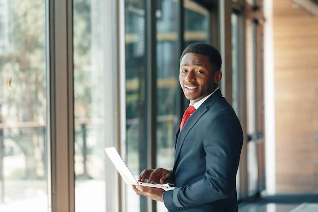 Przystojny młody afro amerykański biznesmen w klasycznym garniturze trzyma laptopa i uśmiecha się