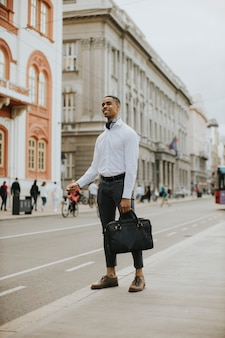 Przystojny młody afroamerykański biznesmen czeka na taksówkę na ulicy