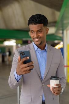 Przystojny młody afrykański biznesmen na zewnątrz niosący filiżankę kawy na wynos, pionowe ujęcie