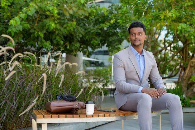 Przystojny młody afrykański biznesmen siedzi na zewnątrz podczas myślenia