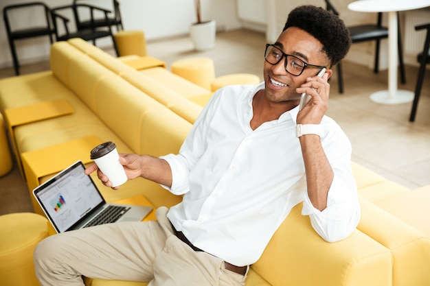 Przystojny młody afrykański mężczyzna opowiada telefonem pije kawę.