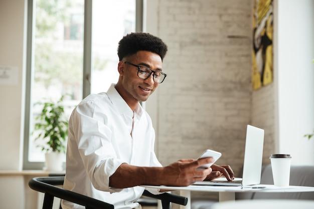 Przystojny młody afrykański mężczyzna siedzi coworking