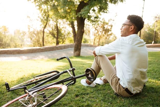 Przystojny młody afrykański mężczyzna siedzi w parku outdoors