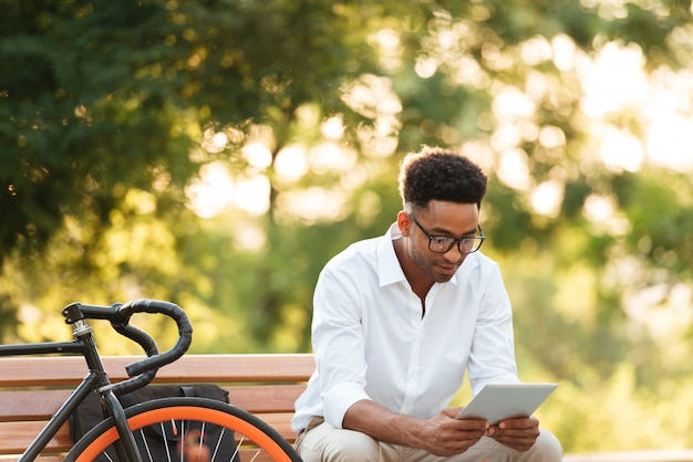Przystojny młody afrykański mężczyzna używa pastylka komputer.