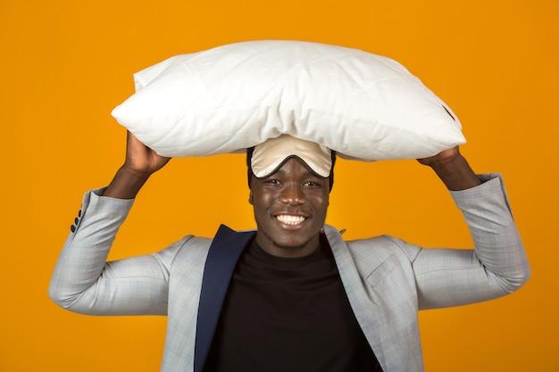 Przystojny młody afrykański mężczyzna w kurtce, ubrany w maskę snu z poduszką w dłoniach
