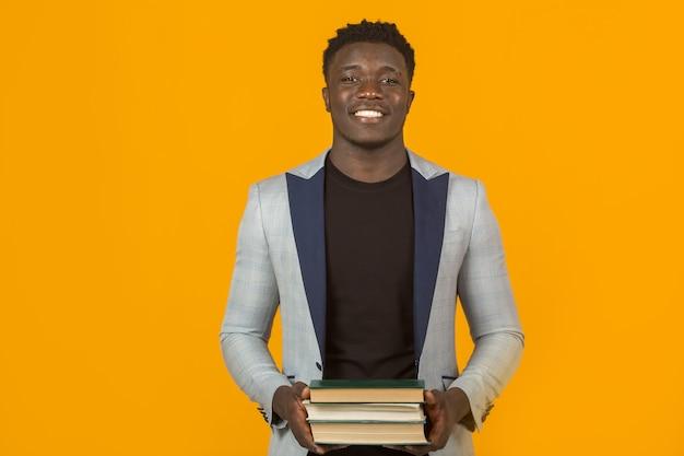 Przystojny młody afrykański mężczyzna w kurtce, z książkami