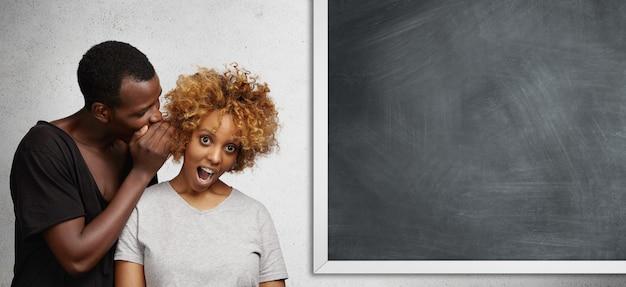 Przystojny młody afrykański student w czarnej koszulce stoi przy tablicy, szepcząc coś do ucha stylowej dziewczyny, dzieląc się najnowszymi plotkami.