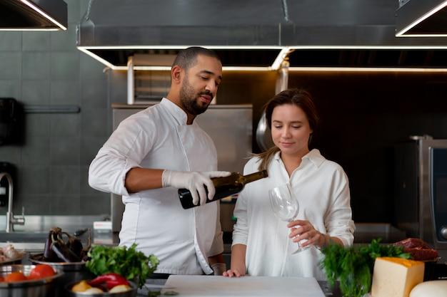 Przystojny młody afrykański szef kuchni gotuje razem z dziewczyną rasy białej w kuchni przy użyciu czerwonego wina. kucharz uczy dziewczynę, jak gotować. mężczyzna i kobieta gotowania w profesjonalnej kuchni.