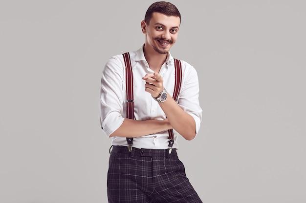 Przystojny młody arabski hipster z białą koszulę i szelki