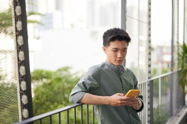 Przystojny młody azjatycki mężczyzna trzyma smartfon, odwracając wzrok i myśląc, stojąc na zewnątrz