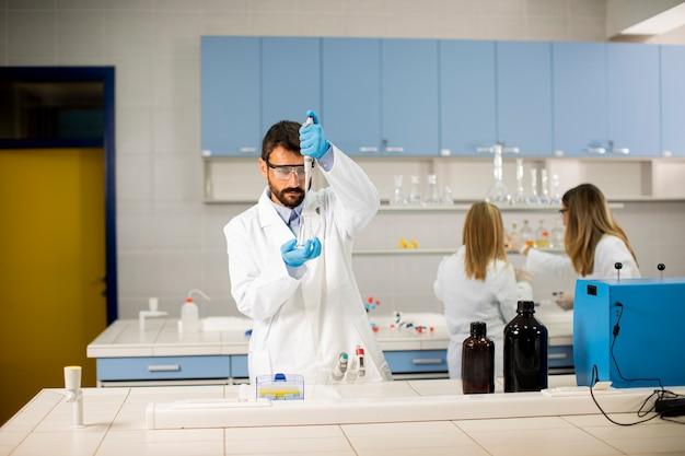 Przystojny młody badacz w ochronnej odzieży roboczej stoi w laboratorium i analizuje kolbę z płynem