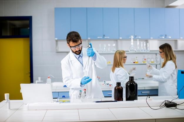 Przystojny młody badacz w ochronnej odzieży roboczej w kolbie do analizy laboratoryjnej