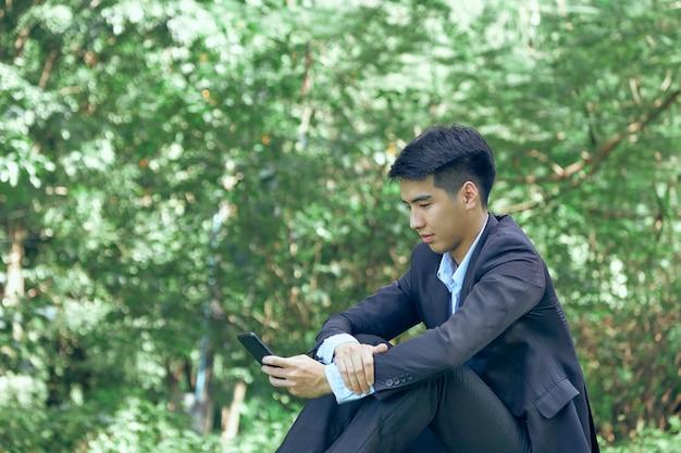Przystojny młody biznesmen azjatyckich siedzi w parku
