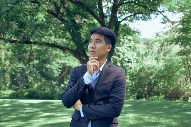 Przystojny młody biznesmen azjatyckich stojący w parku