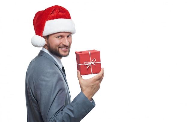 Przystojny młody biznesmen brodaty w kapeluszu christmas przedstawiający mały prezent pod choinkę, uśmiechając się radośnie
