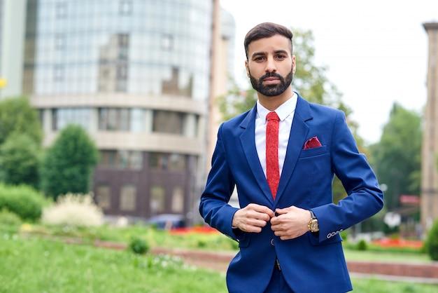 Przystojny młody biznesmen guziki jego kurtki na zewnątrz miasta na
