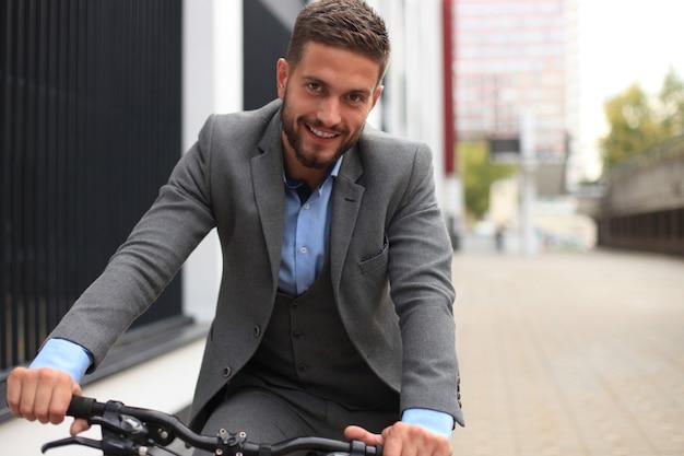 Przystojny młody biznesmen jazda rowerem na zewnątrz w mieście.