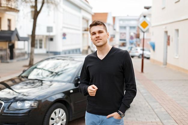 Przystojny młody biznesmen mężczyzna w pobliżu czarnego samochodu na ulicy