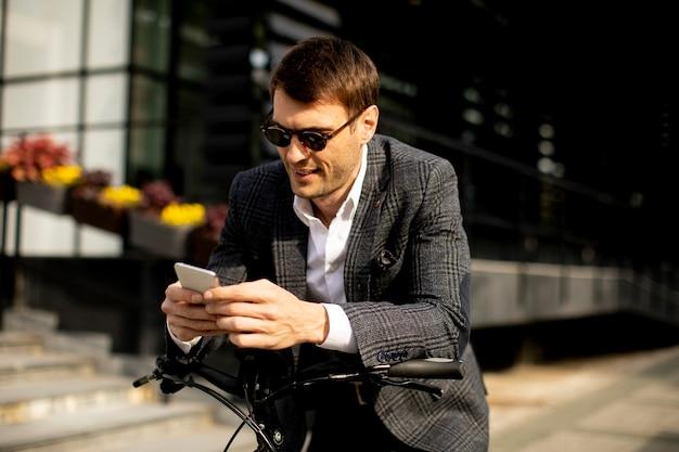 Przystojny młody biznesmen na ebike za pomocą telefonu komórkowego
