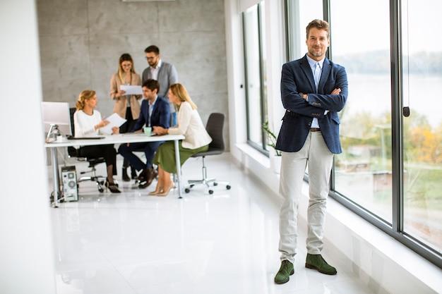 Przystojny młody biznesmen pewnie stoi w biurze przed swoim zespołem