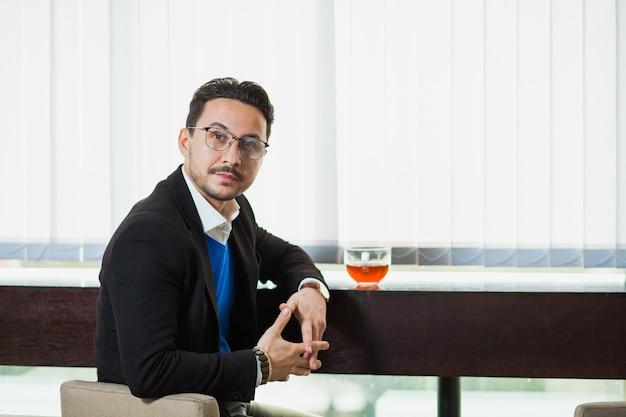 Przystojny młody biznesmen pije herbatę